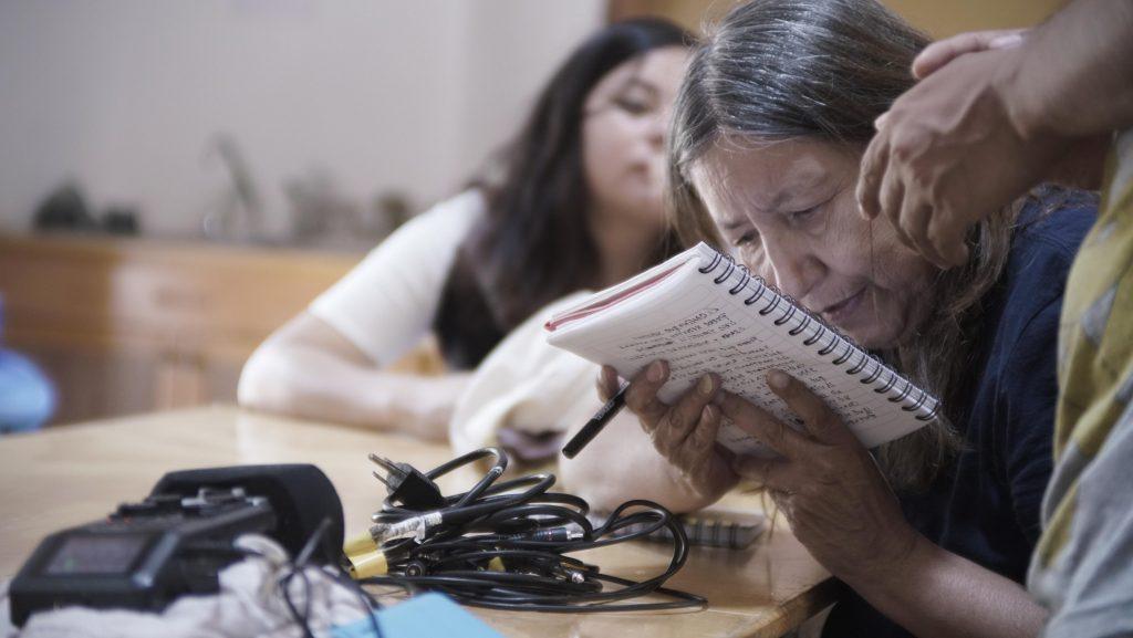 Laura, una mujer de alrededor de 60 años lee la libreta muy cerca de su cara