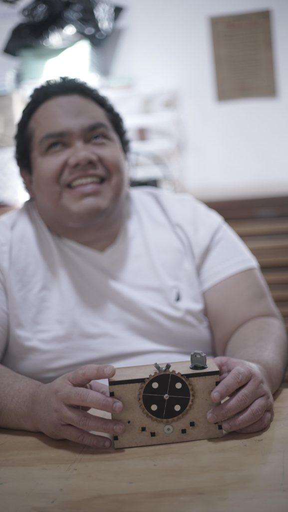 fotografía de pedro miranda, fotografo oaxaqueño sonriendo con una cámara de madera en sus manos