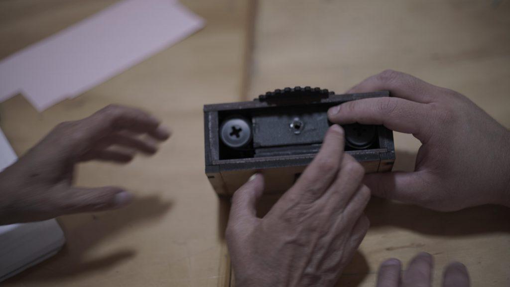 una cámara de madera sobre la mesa, varias manos la tocan y la reconocen
