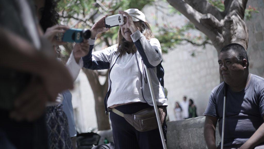 Laura detiene su bastón con el brazo y con las manos sostiene su celular para sacar una fotografía.