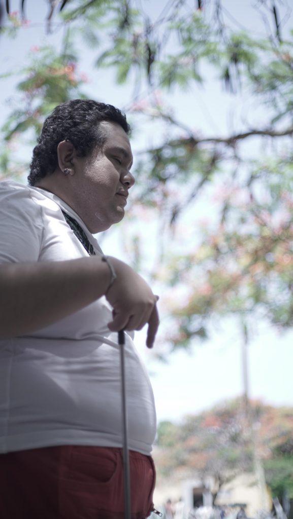 pedro está parado sosteniendo su bastón bajo un árbol